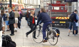 Cyclist riding on the pavement in central London