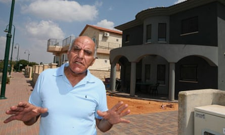 Israeli settler Benny Raz stands in front of a house in the West Bank settlement of Karnei Shomron