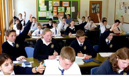 Junior school children in classroom with raised hands