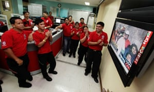 Workers from the Philippines Red Cross watch live coverage of the Chilean miners' rescue, in Manila
