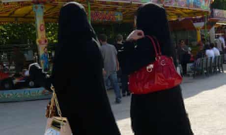 Women wearing niqabs walk in the Tuileries Garden in Paris