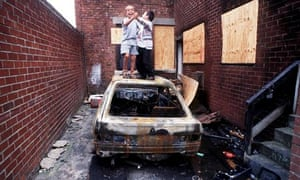Children play on a burned-out car in Benwell, Tyneside, north-east England