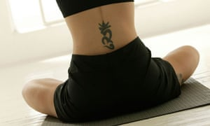 Woman with tattoo performing yoga