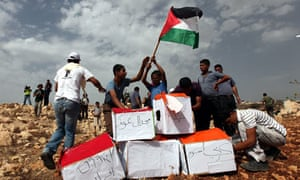 Palestinian and foreign activists prepare to burn boxes depicting Jewish settlements