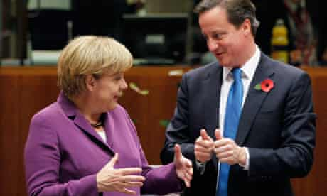 German Chancellor Merkel talks to Britain's PM Cameron during an EU leaders summit in Brussels