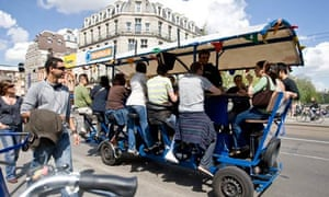 Tourists cycle as they drink beer and sing karaoke on a beer bike in Amsterdam