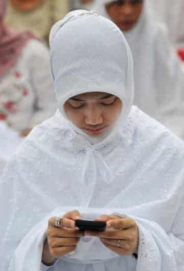 An Indonesian woman checks her mobile