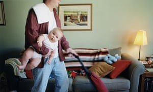 Father does housework while holding baby
