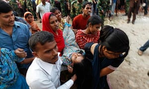 Garment workers carry an injured colleague after a fire at their factory in Ashulia, Bangladesh.