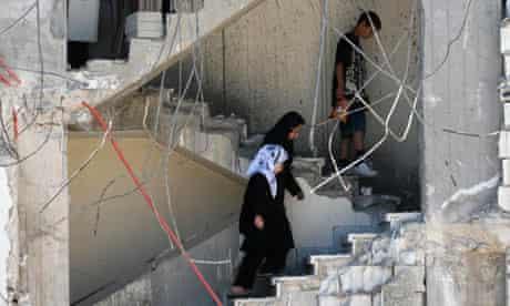 Lebanese civilians walk inside damaged building in Yaroun village