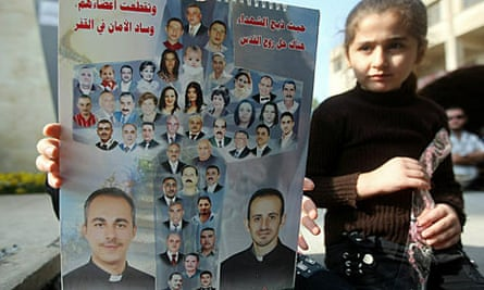 An Iraqi Christian holds a poster showing the victims of the church attack