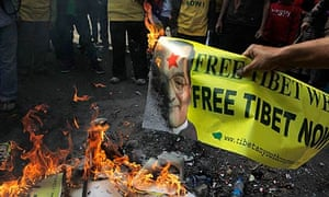A Tibetan activist burns a poster of Chinese Premier Wen Jiabao in New Delhi