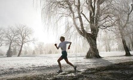 Woman jogs through park in winter