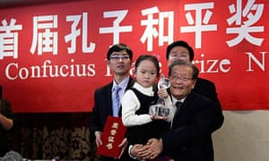 A girl named only as an 'angel of peace'  holds the first Confucius peace prize trophy