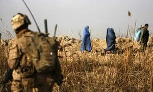 A US marine watches an Afghan family evacuate Trikh Nawar