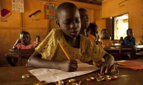 A girl uses bottle tops to count in maths lesson at Brepaw Kpeti Presby, Asesewa, Ghana