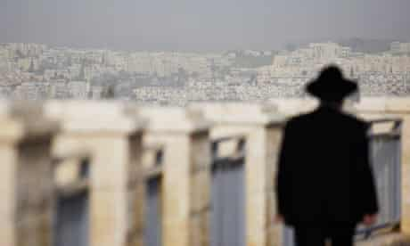 An ultra-Orthodox Jewish man walks in East Jerusalem, where Israel plans to build 1,600 homes.