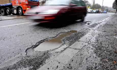 A car passes a pothole on a road in Bristol, January 2010