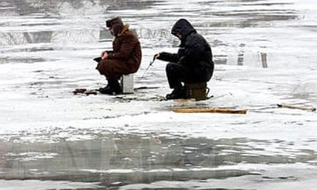 Two enthusiasts ice fishing at the outskirts of Moscow.