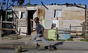 A young boy plays with a ball on the street near a house in the town ship of Khayelitsha