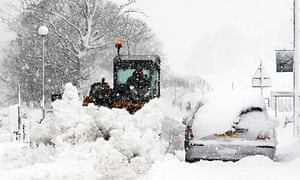 A farmer clears snow from the main street in Carronbridge, central Scotland