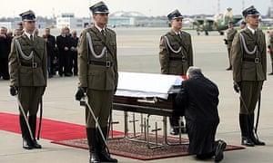 Jaroslaw Kaczynski kneels next to the coffin of his twin brother, Polish president Lech Kaczynski