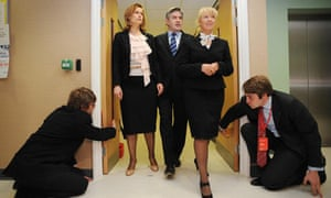 Two unidentified aides crouch down to open doors for Gordon Brown, his wife Sarah and Sam Prince