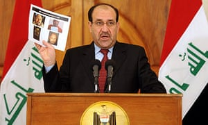 Nouri al-Maliki displays photos of the dead al-Qaida chief at a press conference.