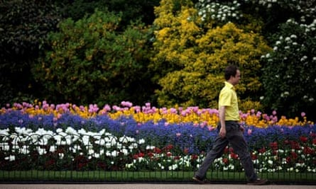 A man walks past flowers as the sun shines in St James's park, London.