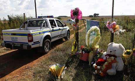 A police vehicle drives past flowers placed at  the entrance of Eugene Terre'Blanche's farm.
