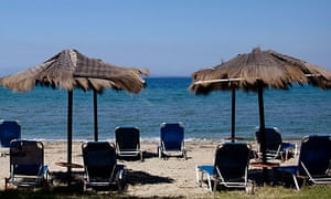 Sunloungers remain empty on a beach on the island of Lesbos, Greece