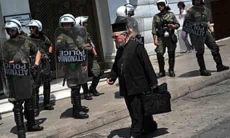 A Greek Orthodox priest walks past riot