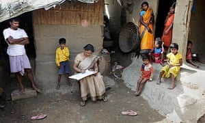Indian census worker Rumnima Das takes information on Mahesh Shah (l), and his family