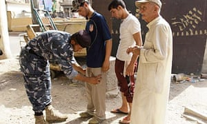 A policeman frisks residents near the site of Sunday's bomb attack in Baghdad