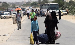 Palestinians carry their luggage to the Rafah border crossing between Egypt and Gaza.