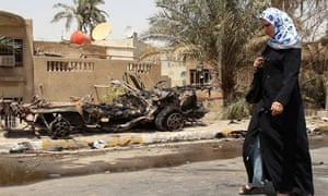 A woman walks past a damaged vehicle at the site of a bombing on the Trade Bank of Iraq in Baghdad.