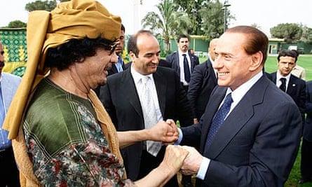 Libyan leader Muammar Gaddafi welcomes the Italian prime minsiter, Silvio Berlusconi, to Tripoli