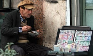 A money changer displays bank notes in Tehran, Iran, 2008.