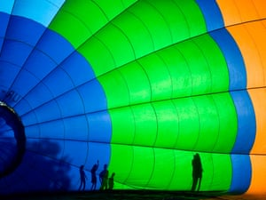 People stand behind a hot air balloon during an international balloon festival in Logoisk