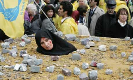 An Iranian woman, symbolically dressed up as a victim of death by stoning, takes part in a protest