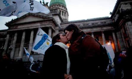 A lesbian couple kisses outside Argentina's congress during a rally to support same-sex marriage.