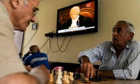 Kosovo Albanians play chess and watch TV in Pristina as judges rule on Kosovo's UDI.