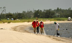 BP clean-up workers collect tar balls an