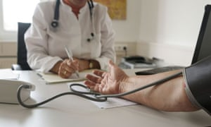 Doctor takes patients blood pressure-detail
