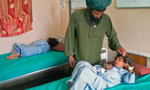 An Afghan man talks to his wounded child at a hospital in southern Kandahar city.