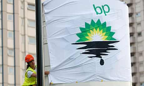 A Greenpeace activist puts up a banner as they block off a BP fuel station.