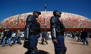 Police officers patrol outside Soccer City in Johannesburg, South Africa before a match.