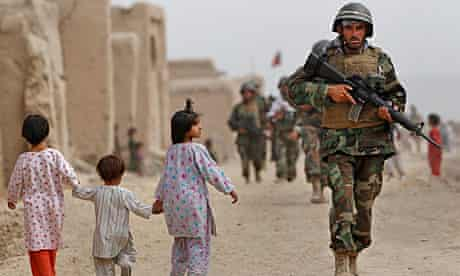 A Nato soldier passes children in the village of Bazaar e Panjwaii, Kandahar province.