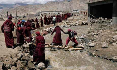 Monks conduct a rescue operation after flash floods at Choklansar, on the outskirts of Leh