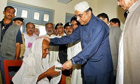 President Asif Ali Zardari presents a cheque to an elderly flood survivor on a visit to Sukkur.